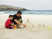 Father and son building sand castles on the beach. Stock Photography