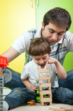 Father and son building a wooden toy tower Royalty Free Stock Photo