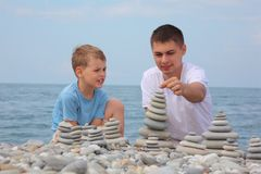 Father and son builds stone stacks on beach Stock Photography