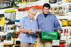 Father And Son Buying Tools In Hardware Store. Father and son with checklist buying tools in hardware store Royalty Free Stock Photo
