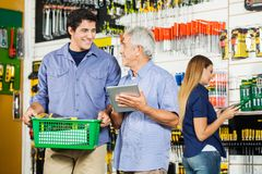 Father And Son Buying Tools In Hardware Store. Father and son with digital tablet buying tools in hardware store with female customer in background Royalty Free Stock Image