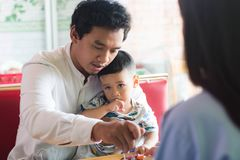 Father and his son sitting and eating cake at indoors cafe. In the morning royalty free stock photography