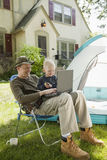 Father and son camping. In the front yard with laptop computer Stock Photos