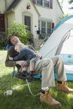 Father and son camping. Father sleeping with son in his lap while camping in the front yard r Royalty Free Stock Images