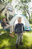 Father and son camping. Father and son pitching a tent in the front yard Stock Photo