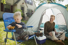 Father and son camping. Father with laptop and son playing while camping in the front yard Royalty Free Stock Photography