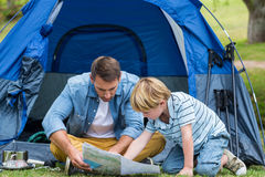 Father and son camping and looking for their way home. On a sunny day Stock Photography