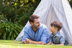 Father and son camping. Father and son lying with their head outside the tent. Smiling men and happy cute boy playing the indians with the tent in a garden.. Man Royalty Free Stock Image