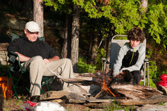 Father and son camping. Father and son sitting by a campfire roasting marshmallows Stock Photography
