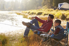 Father and son on a camping trip fishing by a lake stock photos
