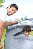 Father and son camping. A 35 years old men and a little boy inside a canvas tent Royalty Free Stock Images