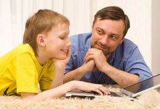 Father and son on the carpet with laptop Stock Photos