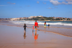 Father and son carrying their surfboard on the beach. SANTANDER, SPAIN - AUGUST, 20: Father and son carrying their surfboard on the beach on August 20, 2016 Stock Photography