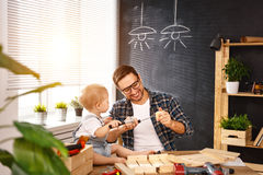Father and son carved of wood in carpentry workshop royalty free stock images