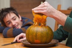 Father and son carving Halloween pumpkin on a kitchen table. Candid shot royalty free stock photography