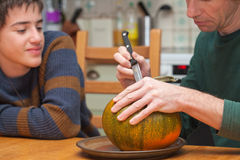 Father and son carving Halloween pumpkin on a kitchen table Royalty Free Stock Photos