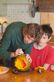 Father and son carving Halloween pumpkin on a kitchen table. Candid shot royalty free stock photos