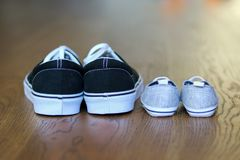 Father and son casual shoes staying next on the wooden floor stock images