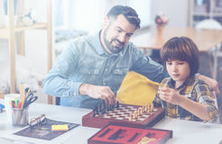 Father and son challenging each other in chess game Royalty Free Stock Photos