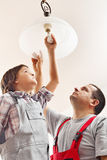 Father and son changing lightbulb in a ceiling lamp. Together royalty free stock photo