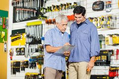 Father And Son Checking Checklist In Hardware Royalty Free Stock Image