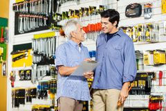 Father With Son Checking List In Hardware Store Stock Image