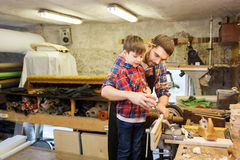 Father and son with chisel working at workshop. Family, carpentry, woodwork and people concept - father and little son with hammer and chisel working with wood stock photography