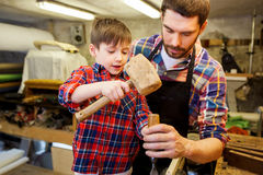 Father and son with chisel working at workshop. Family, carpentry, woodwork and people concept - father and little son with hammer and chisel working with wood stock image