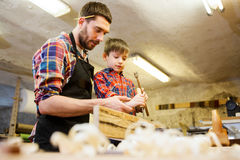 Father and son with chisel working at workshop. Family, carpentry, woodwork and people concept - father and little son with hammer and chisel working with wood Royalty Free Stock Image