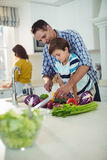 Father and son chopping vegetables in kitchen Stock Photo