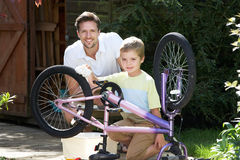 Father And Son Cleaning Bike Together Stock Photography