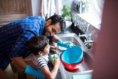 Father and son cleaning utensils at home. High angle view of father and son cleaning utensils at home Stock Photography