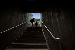 Father and son climbing stairs in pedestrian subway Stock Photos