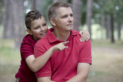 Father Son Closeness. Son is hugging his father and pointing Stock Photography
