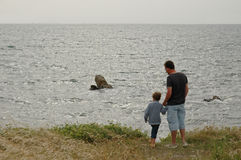 Father and Son at the Coast. Father and son looking at the vastness of the Atlantic Ocean Stock Images