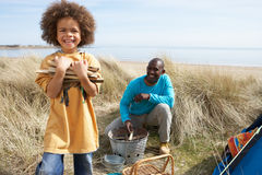 Father And Son Collecting Firewood On Beach. Camping Holiday Stock Photo
