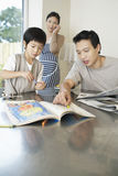 Father And Son Coloring Book And Woman On Call At Home Stock Images
