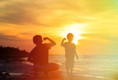 Father and son comparing arm strength at sunset. Sea Royalty Free Stock Photos