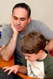 Father son computer. Father teaching his son to work on a computer Royalty Free Stock Image