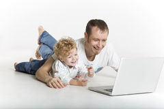 Father and son are on computer on the floor Royalty Free Stock Images