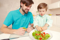 Father and son cook salad Royalty Free Stock Photos
