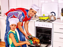 Father and son cooking chicken at kitchen Stock Images