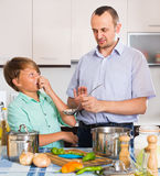 Father and son cooking dinner. Father and his teenage son cooking a dinner and smiling Royalty Free Stock Photography
