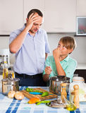 Father and son cooking dinner. Father and teenage son cooking dinner and smiling Stock Image