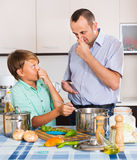 Father and son cooking dinner. Father and teenage son cooking the dinner and smiling Royalty Free Stock Photos