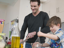 Father And Son Cooking Food In Kitchen Stock Images