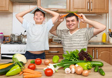 Father and son cooking and having fun with vegetables in home kitchen interior. Two people, man and child. Fruits and vegetables. Royalty Free Stock Photos