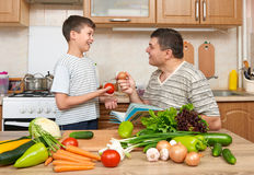 Father and son cooking and having fun with vegetables in home kitchen interior. Two people, man and child. Fruits and vegetables. Royalty Free Stock Images