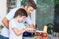 Father and son cooking home kitchen, slicing stock photos