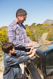 Father and son in the countryside using laptop. On a sunny day royalty free stock photo